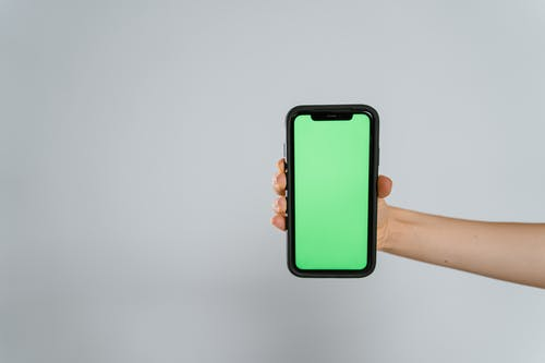 Person Holding Black Iphone 5 With Green Case