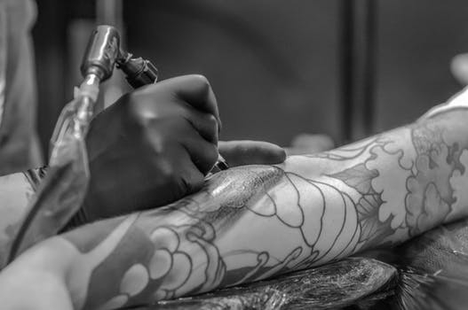 Grayscale Photo of Person Applying Tattoo