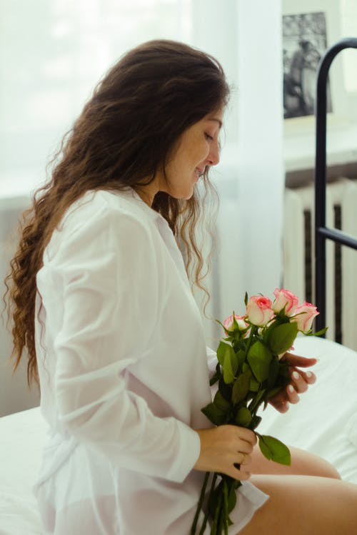 Woman in White Long Sleeve Shirt Holding Pink Rose Bouquet