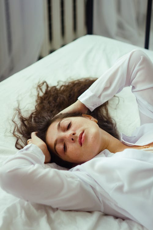 Woman in White Long Sleeve Shirt Lying on White Bed