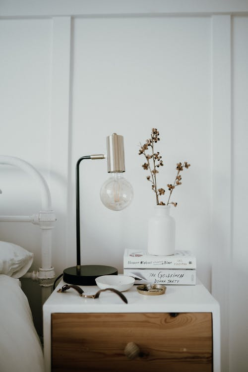 A White Ceramic Vase on the Bedside Table