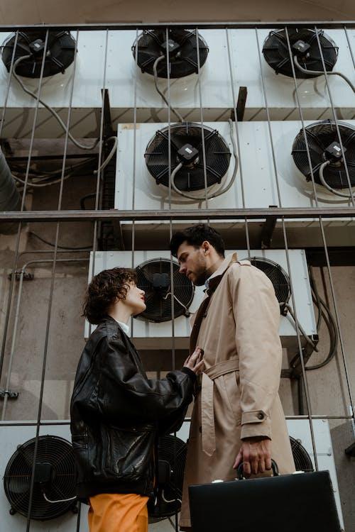 Man in Beige Coat Kissing Woman in Black Leather Jacket