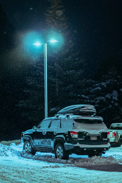 Black Suv on Snow Covered Ground during Night Time