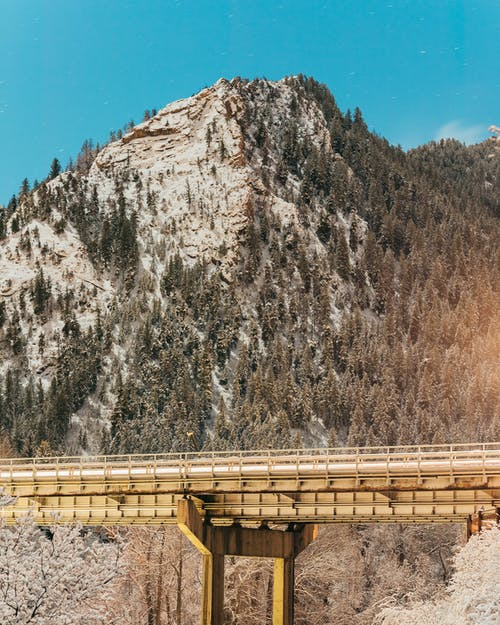 Brown Wooden Bridge Across Gray Mountain