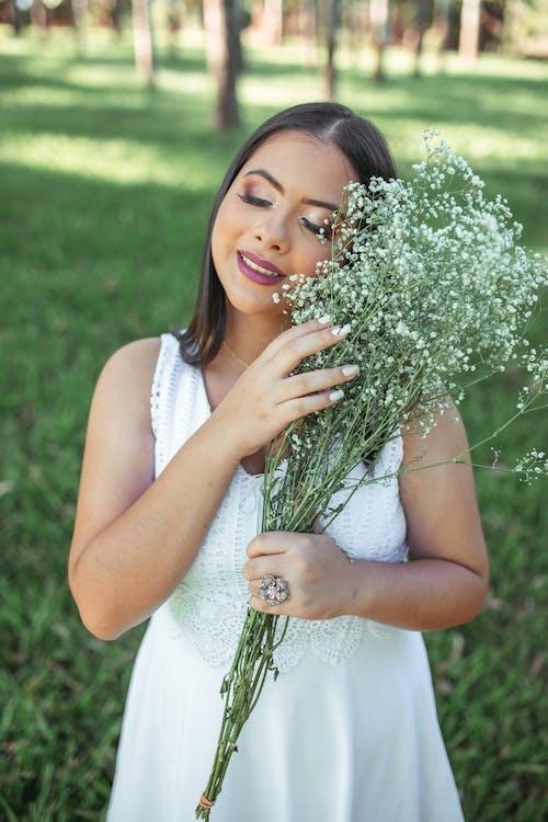 Woman in White Sleeveless Dress Holding White Flowers