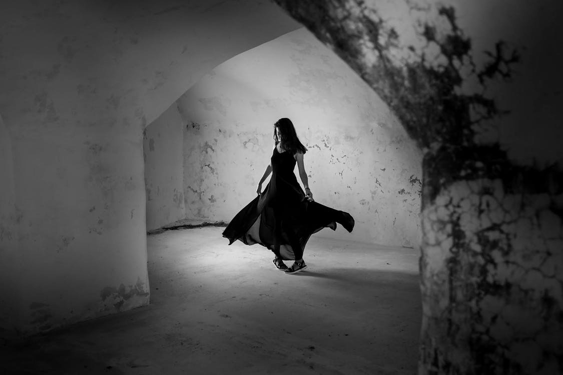Grayscale Photo of Woman in Dress in Concrete Building