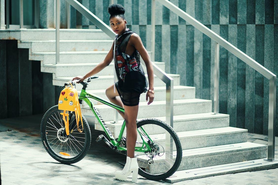 Woman Wearing Black Dress Riding Bicycle Near Stairs