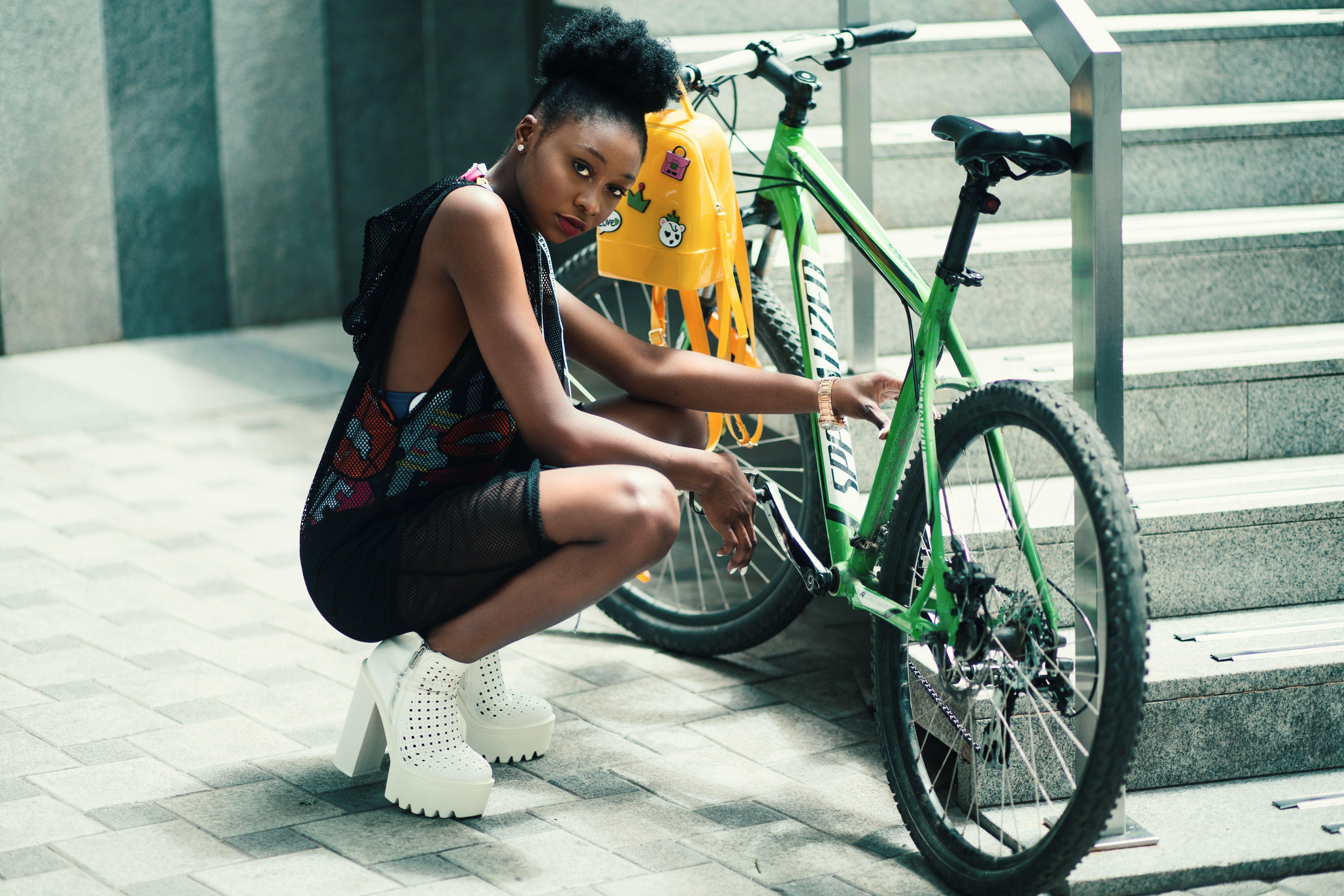 Woman Wearing Black Dress Seating Near Green Bicycle