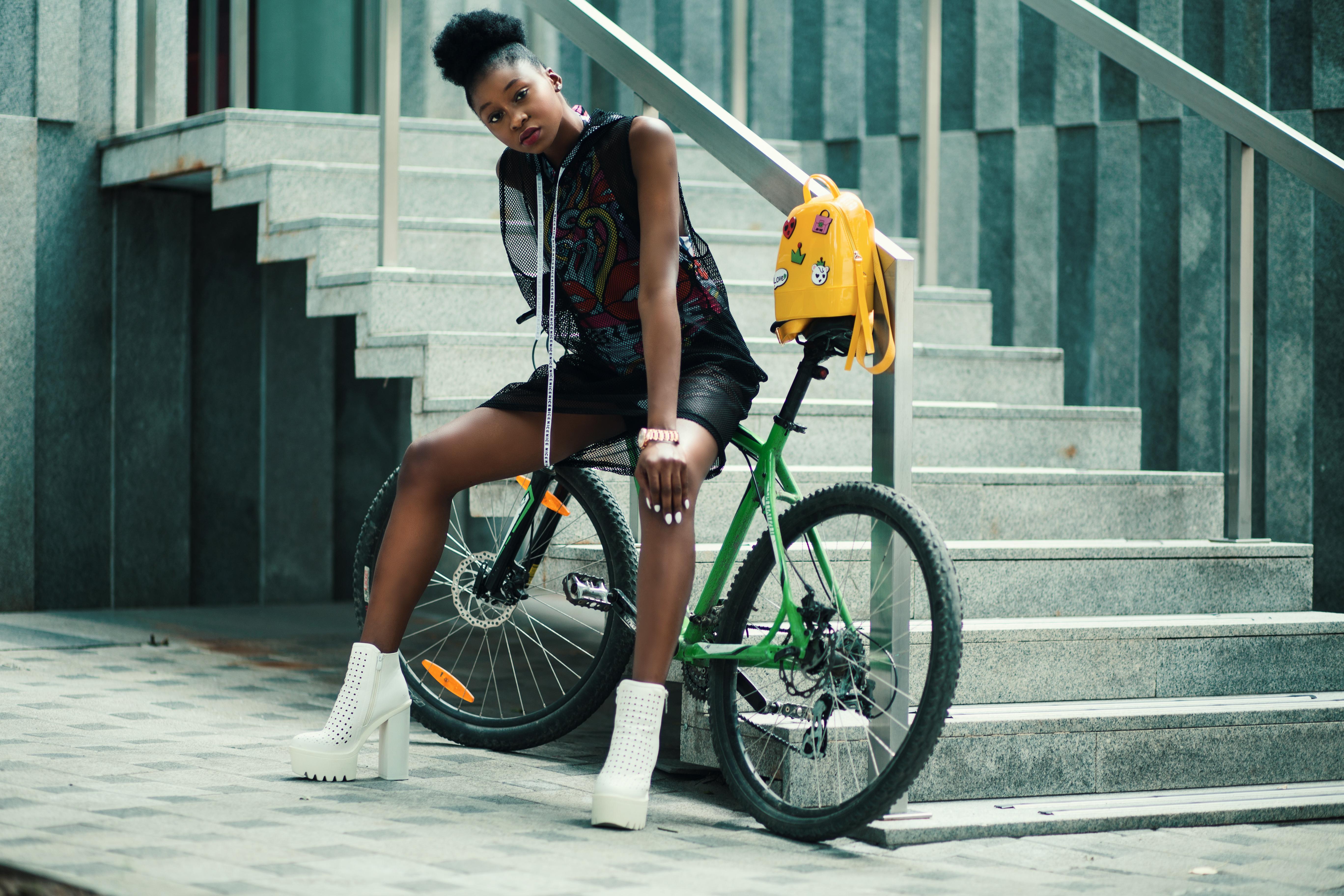 Woman in Black Sleeveless Dress Sitting on Green Bike