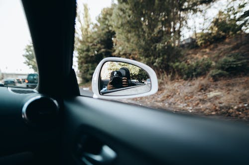 Car Side Mirror Showing Man in Black Sunglasses