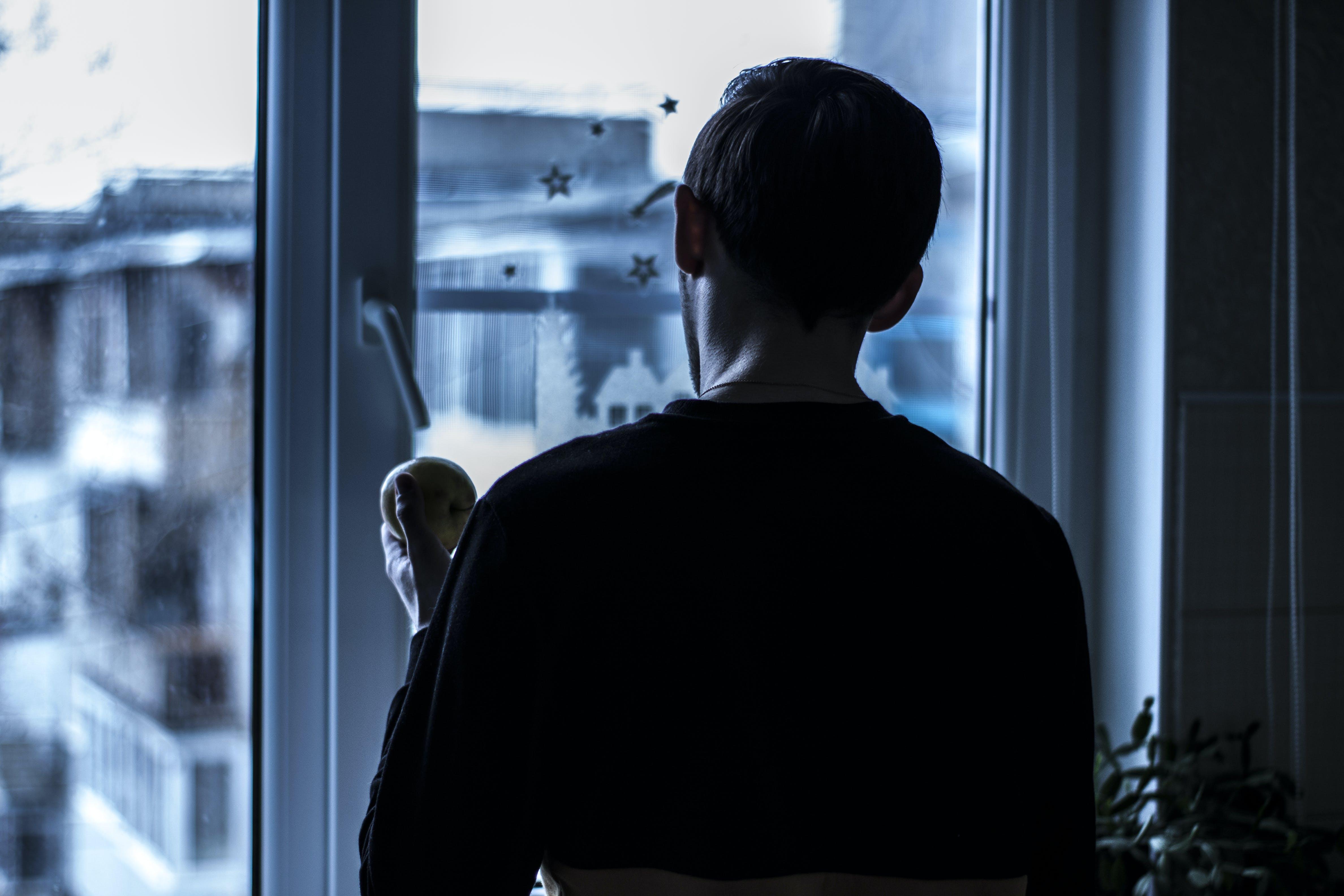 Man Looking Outside Near Clear Glass Window