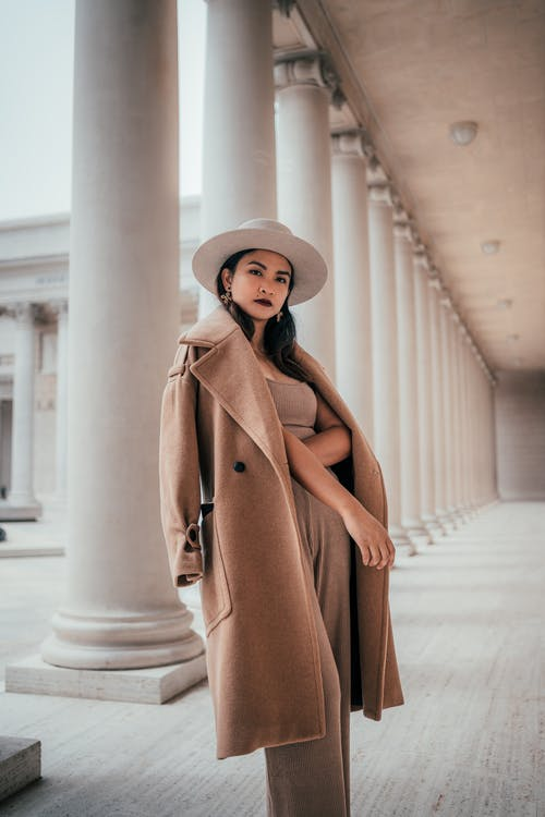 Woman in Brown Coat Standing on White Concrete Staircase