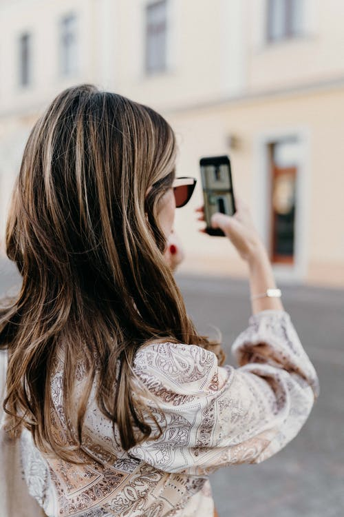 Woman in White Floral Long Sleeve Shirt Holding Black Smartphone