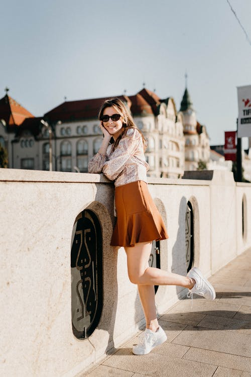 Woman in White Long Sleeve Shirt and Orange Skirt Standing on Gray Concrete Wall