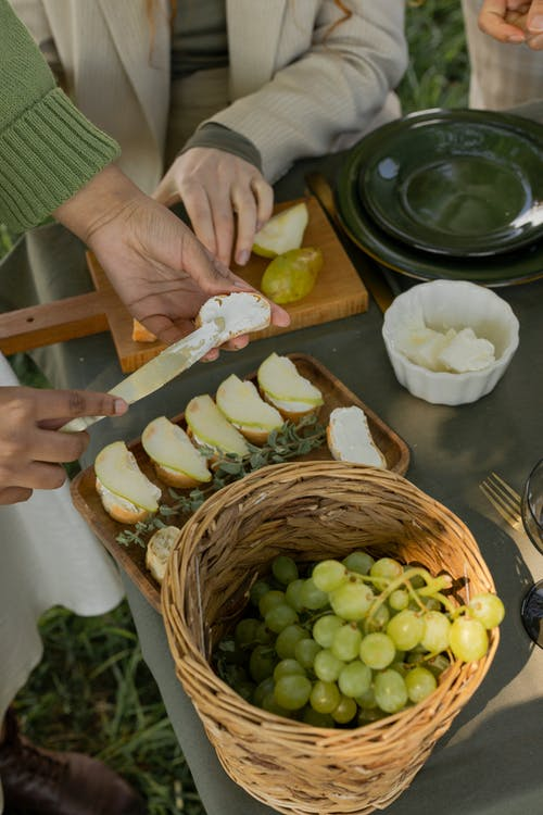 Person Slicing Green Fruit on Brown Wooden Chopping Board