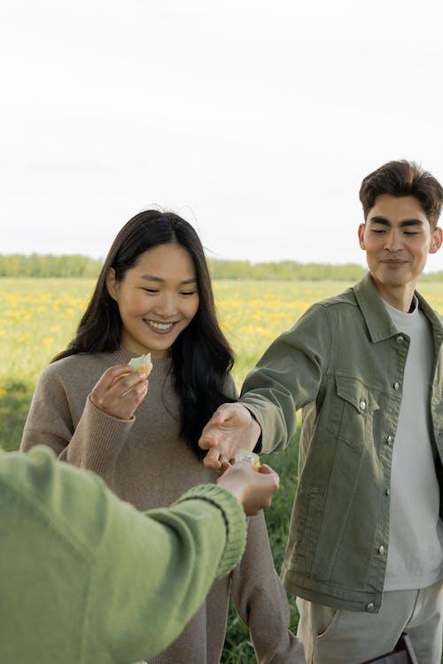 Man in Gray Coat Holding Woman in Green Coat