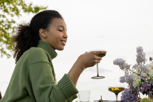 アルコール飲料を保持している緑のセーターの女性