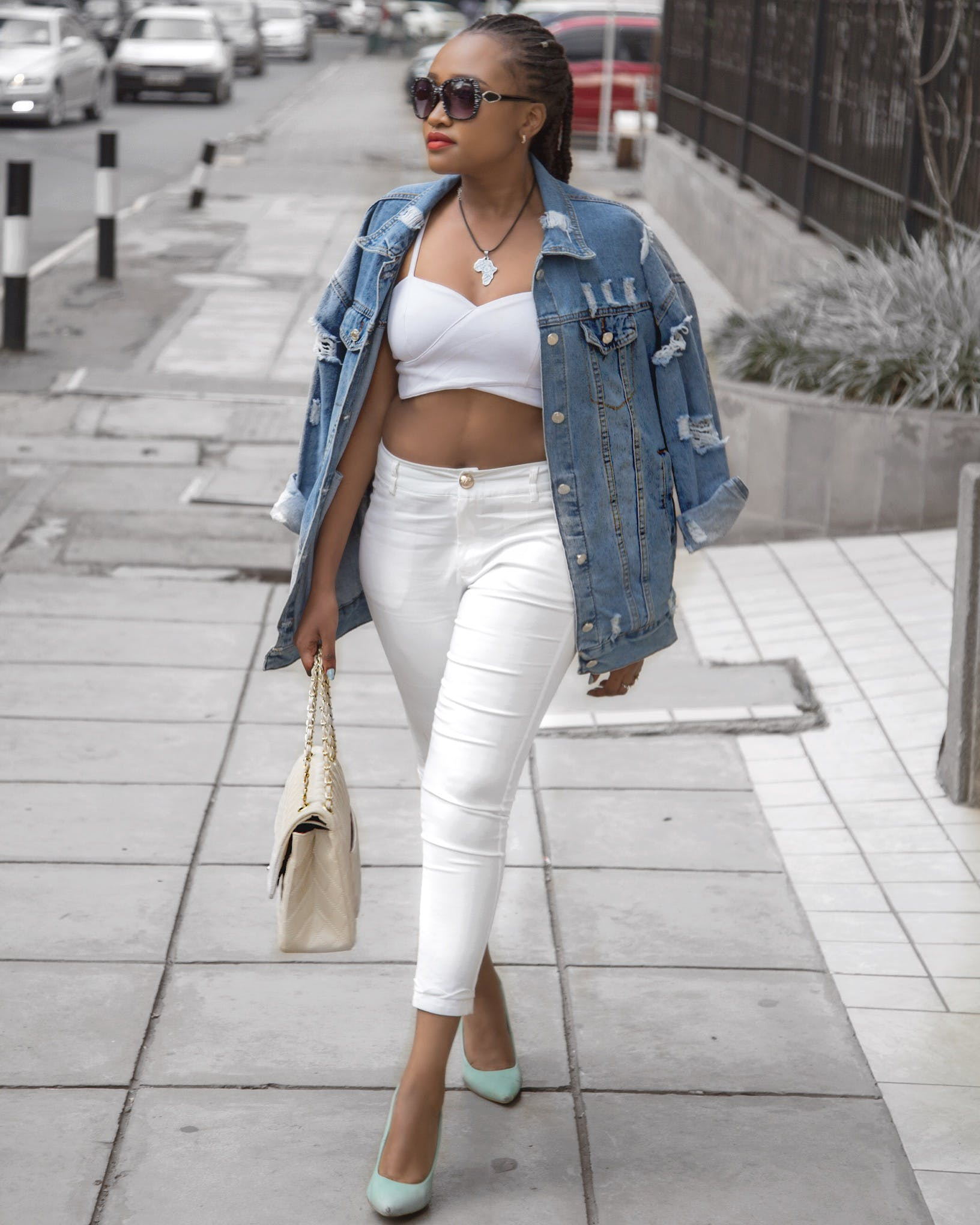 Photo of Woman Wearing White Crop Top and Denim Jacket Walking in Pavement Holding Bag