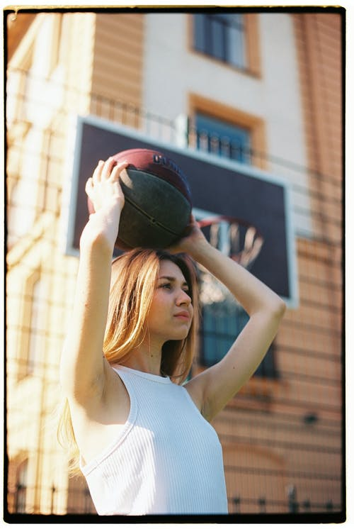Woman in White Tank Top Holding Black and Red Basketball