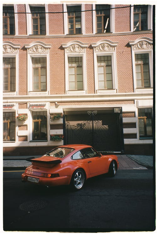 Red Porsche 911 Parked in Front of White Building
