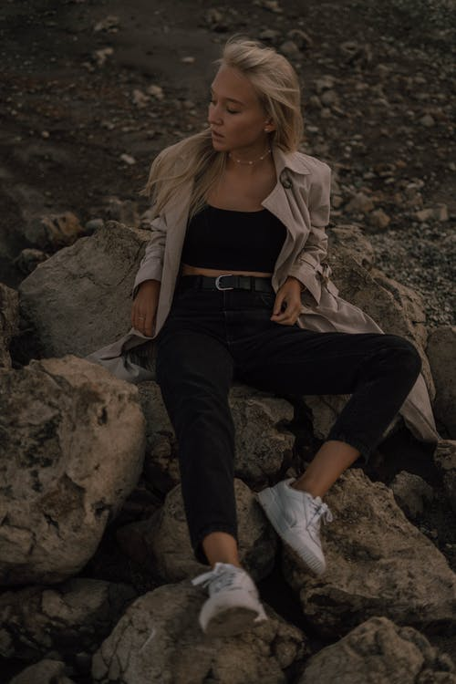 Woman in Gray Jacket and Black Pants Sitting on Gray Rock