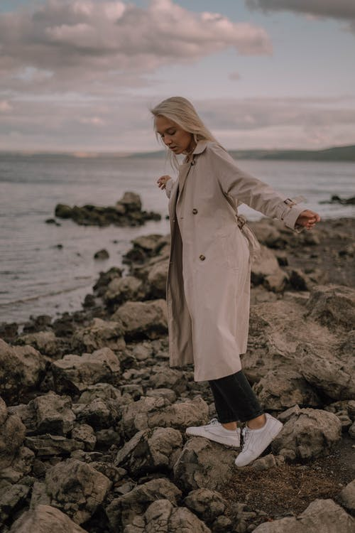 Woman in White Coat Standing on Rocky Shore