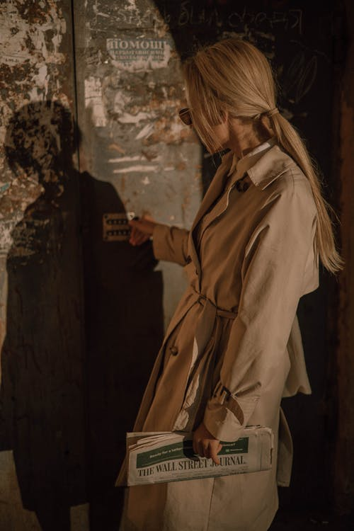 Woman in Brown Coat Standing Beside Wall