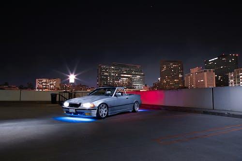 Blue Sedan on Road during Night Time