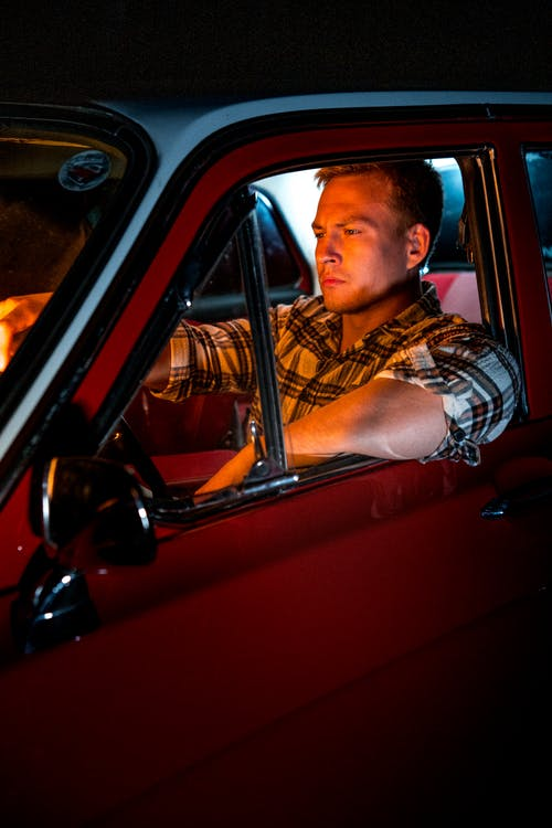 Man in Brown and Black Plaid Button Up Shirt Sitting on Red Car