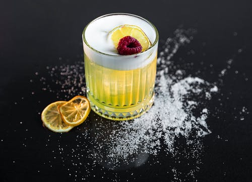 Clear Drinking Glass With Yellow Liquid and Sliced Lemon
