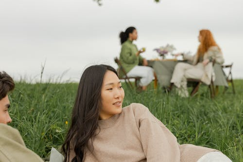Woman in Brown Sweater Sitting on Green Grass Field