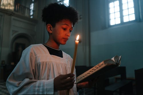 Man in White and Blue Striped Long Sleeve Shirt Holding Lighted Candle