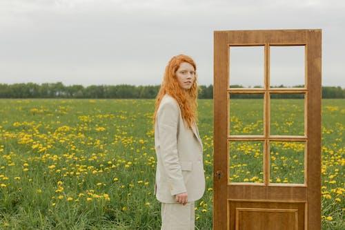 Woman in White Blazer Standing on Yellow Flower Field