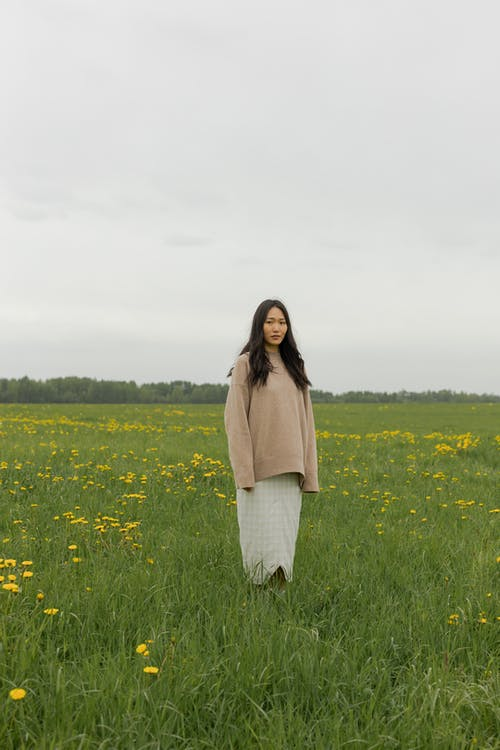 Woman in Brown Coat Standing on Green Grass Field