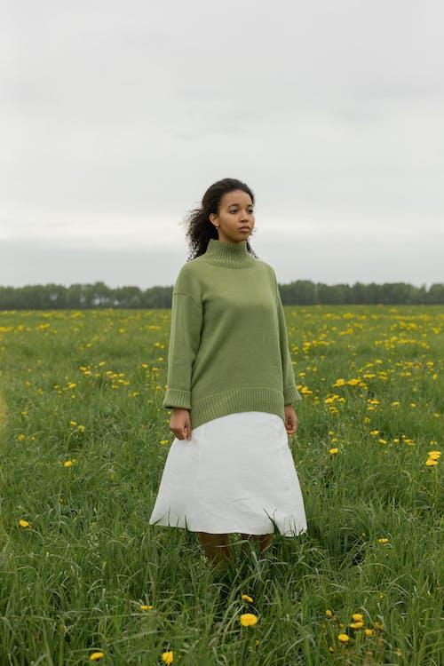 Woman in Green Sweater Standing on Green Grass Field