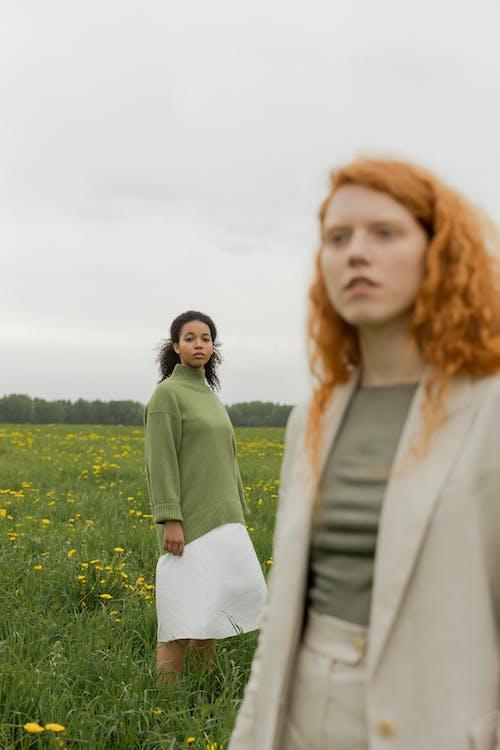 Woman in White Coat Standing Beside Woman in Green Sweater on Green Grass Field