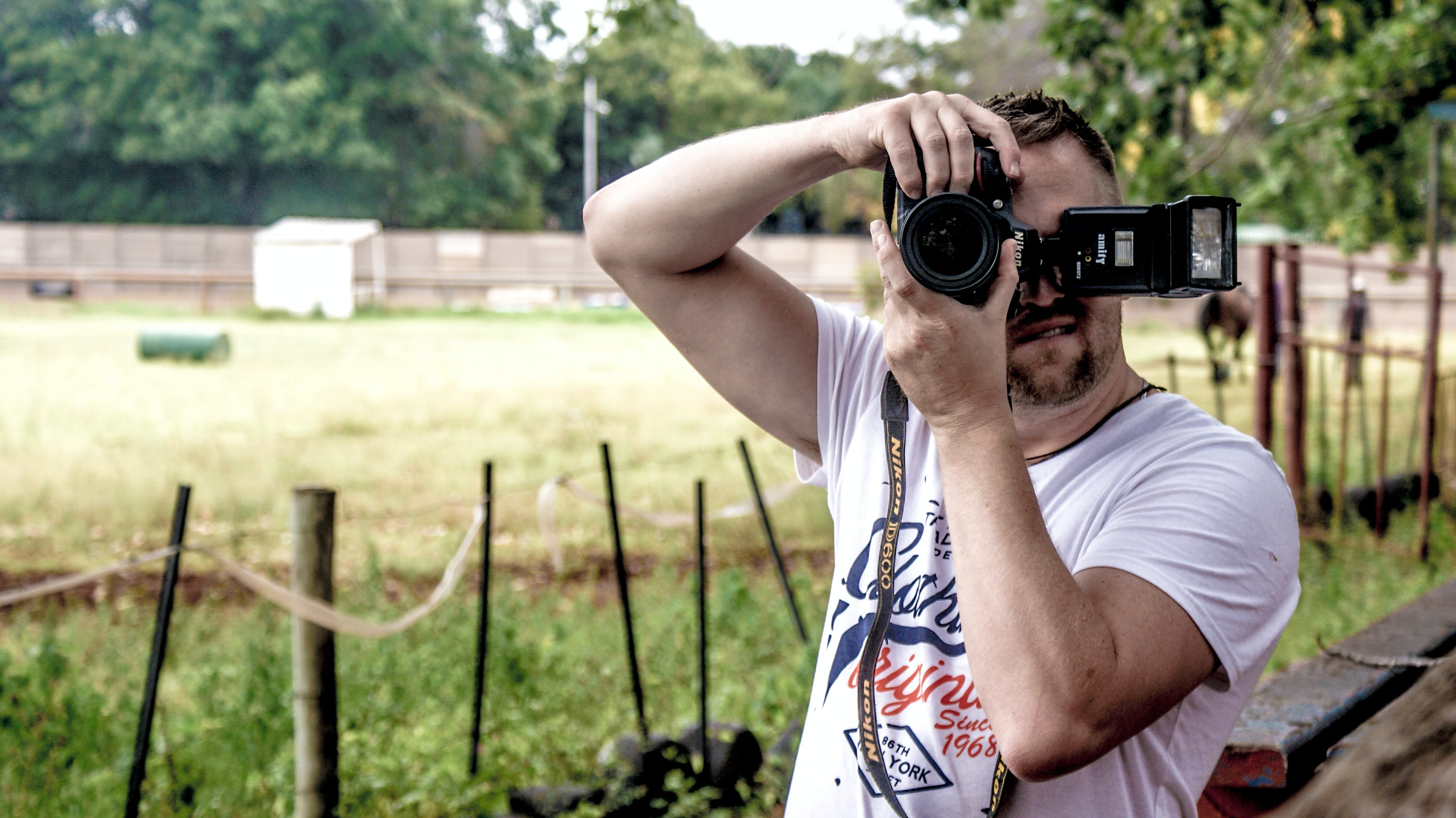 Man Holding Dslr Camera While Standing Near Fence