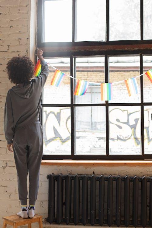 Woman Putting Pride Banderitas on Window