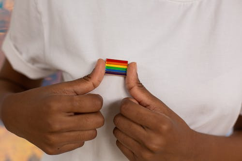 Close-up Photo of Pride Pin on White Shirt