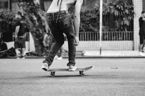 Man in Black Denim Jeans Riding Skateboard