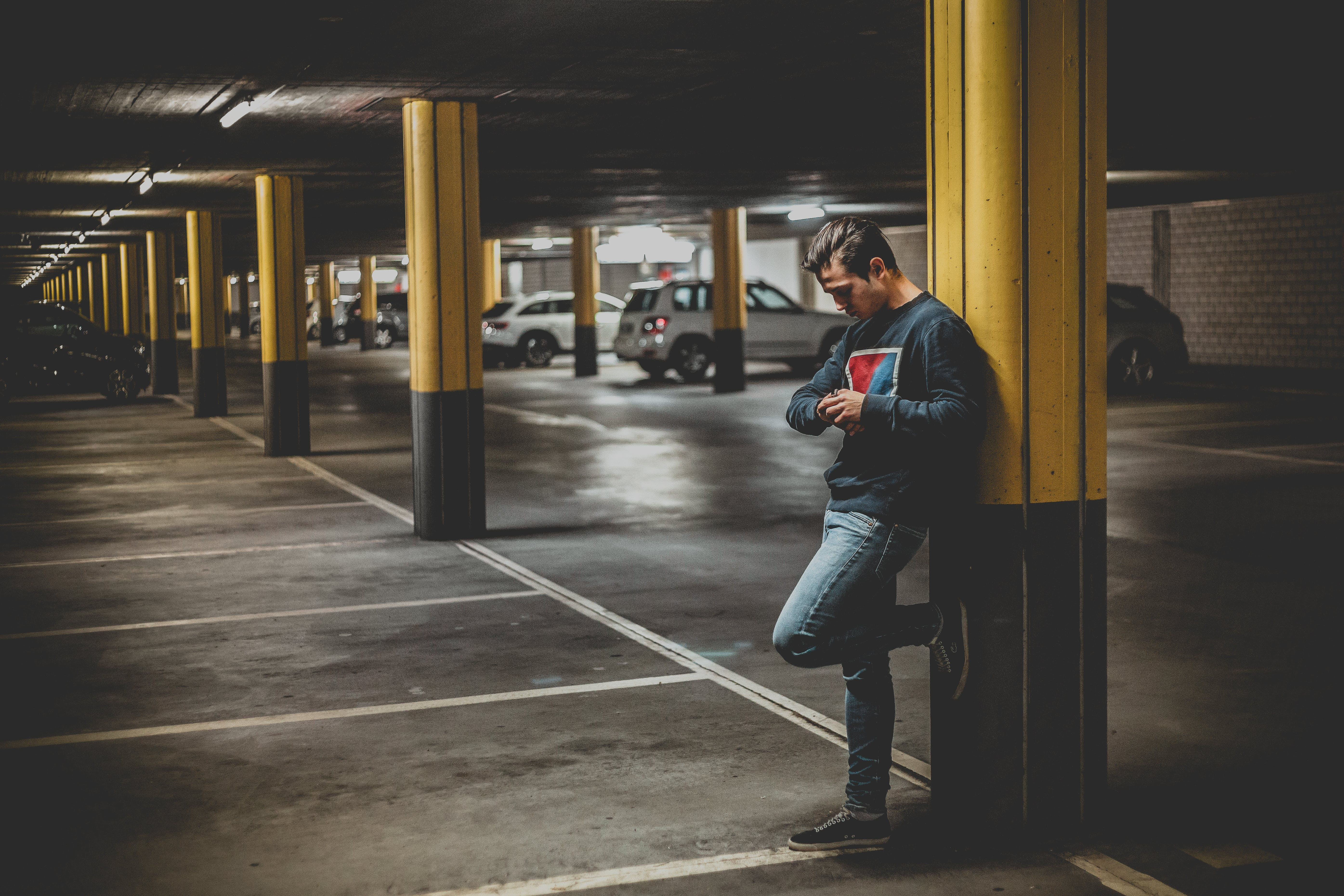 Man in Dark-gray Crew-neck Sweater Standing Leaning to Post in Parking Lot