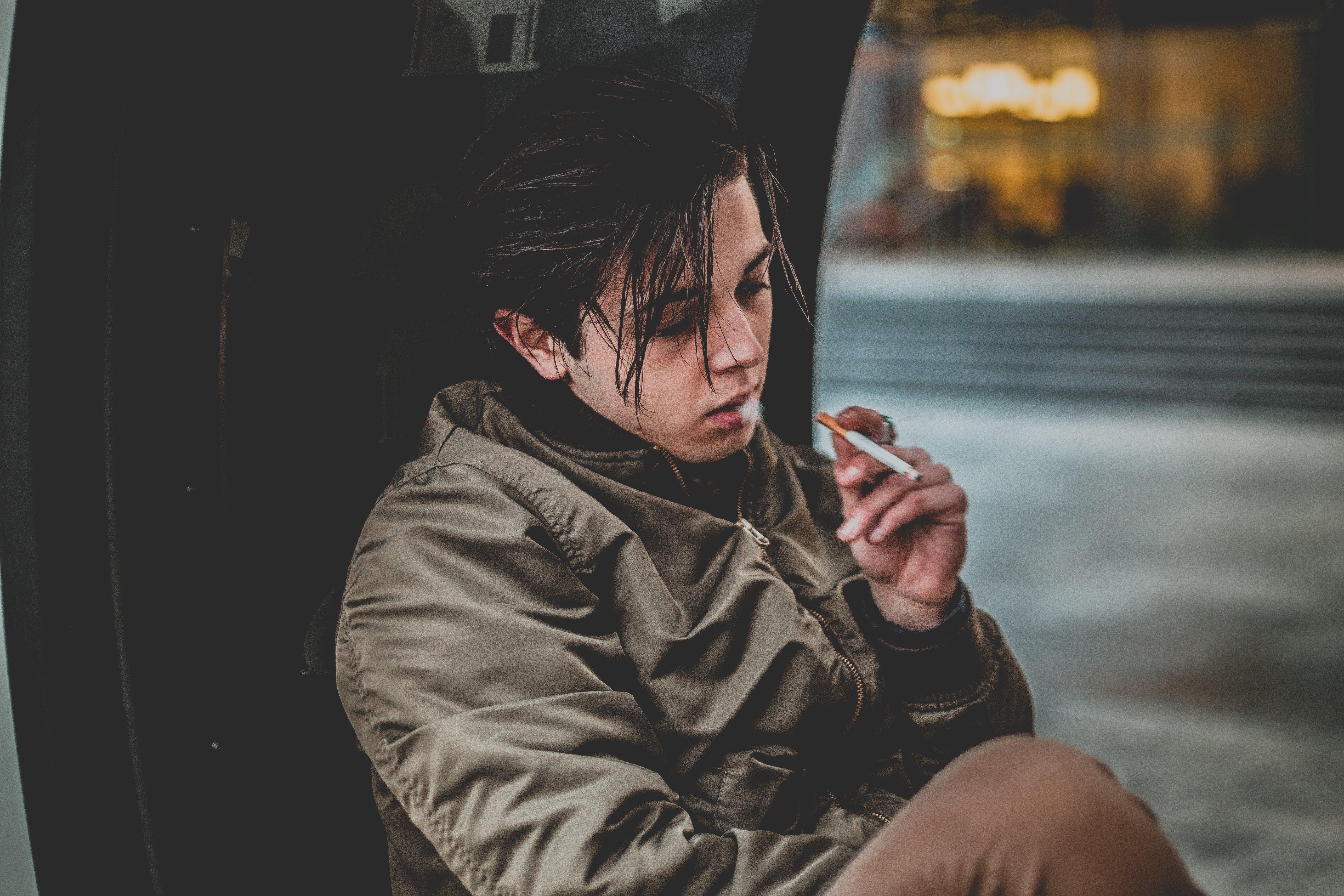 Man Wearing Gray Jacket Holding Cigarette