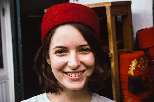 Smiling Woman Wearing Red Knit Cap and Gray Crew Neck Shirt