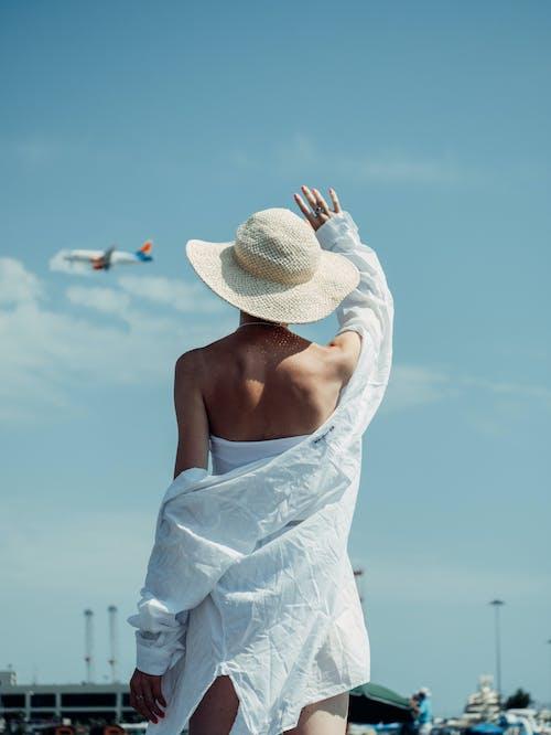 Woman in White Sun Hat Under Blue Sky