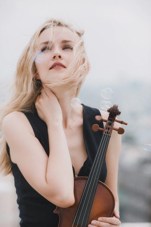 Woman in Black Tank Top Holding Violin