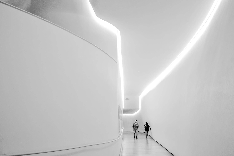 Two Woman Walking Near White Building