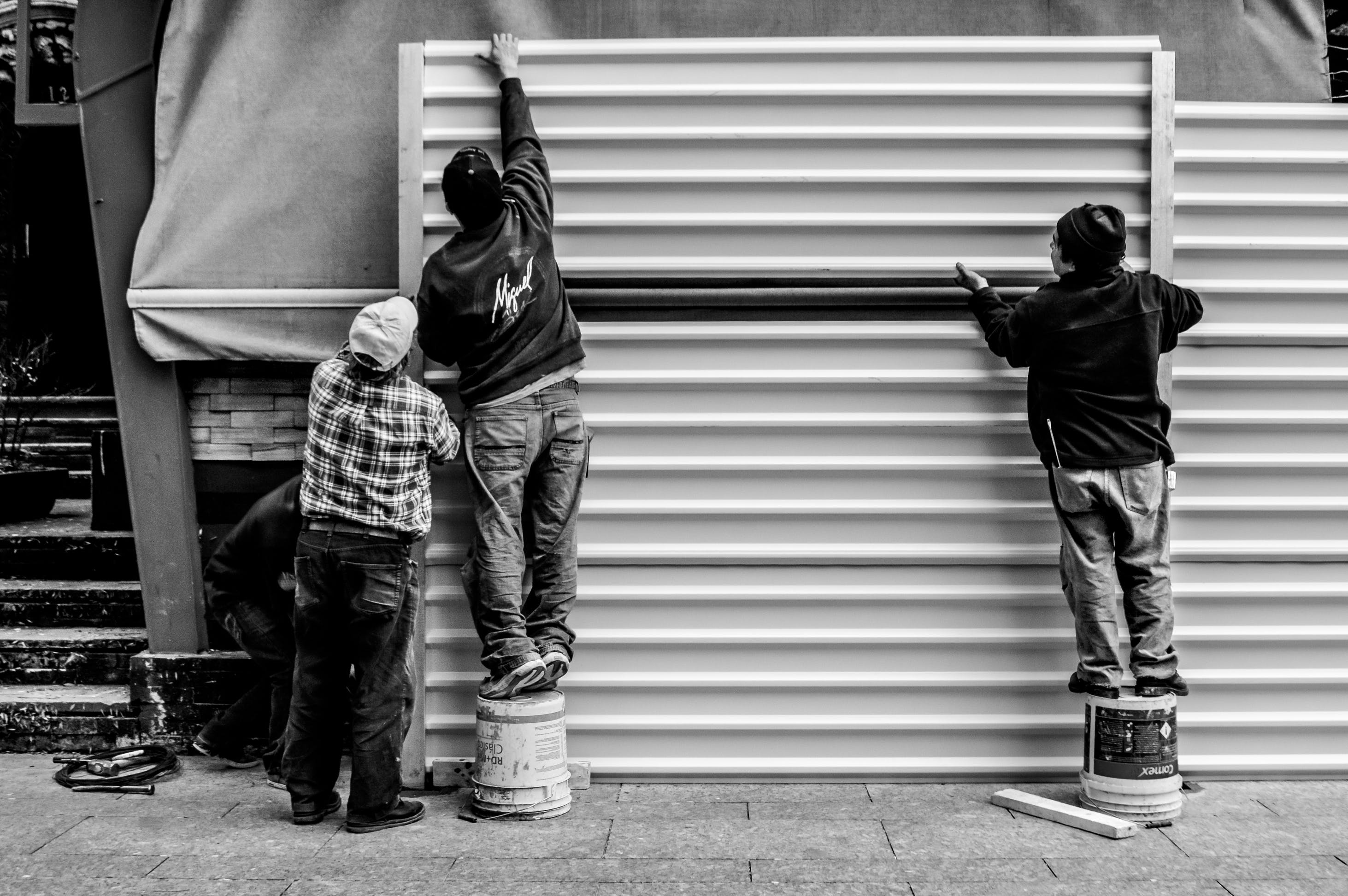 Grayscale Photo of Three Men Arranging Metal Wall