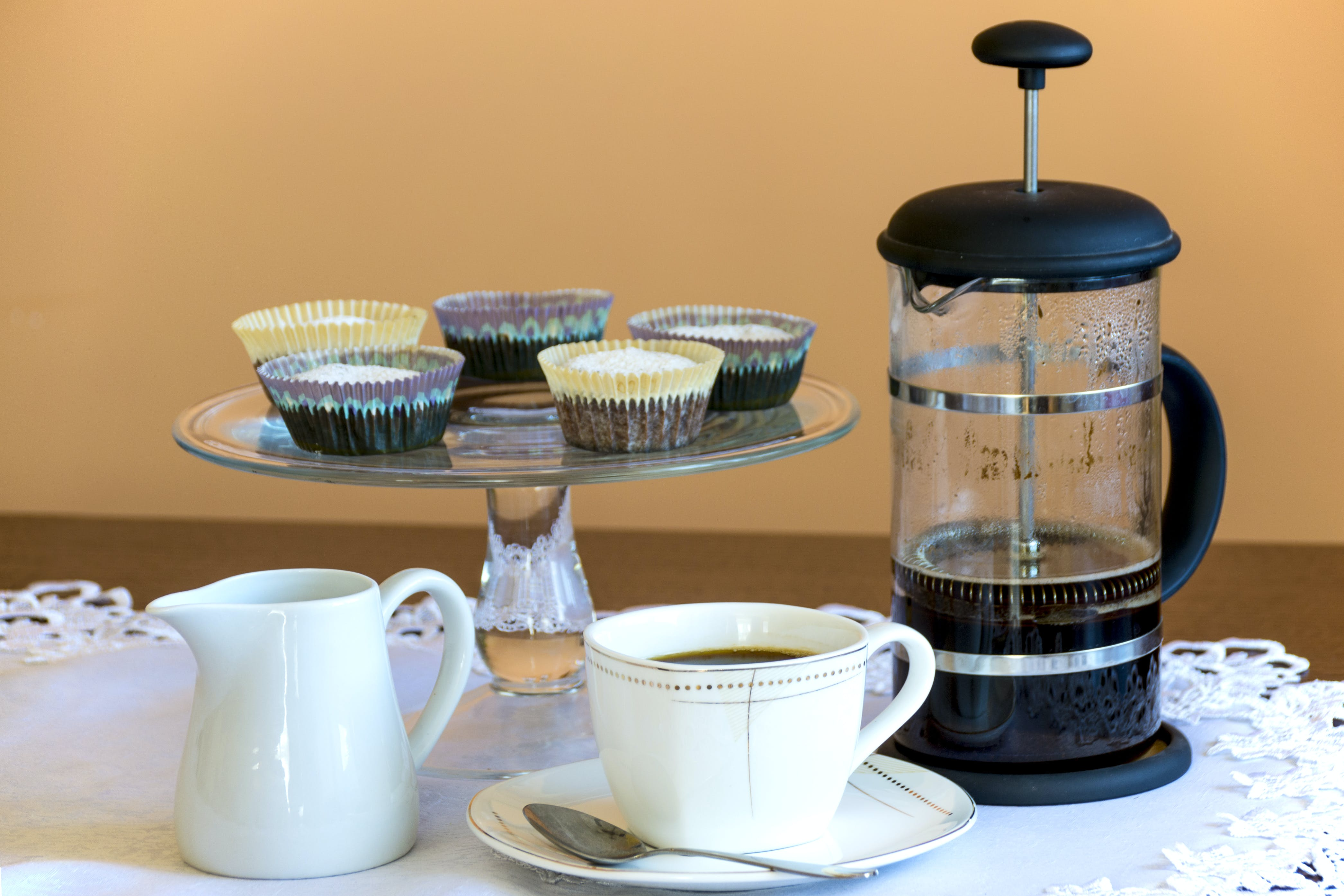 French Press Beside Footed Rack of Cupcakes