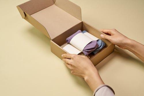 一個人用紙板盒包裝折疊襪
