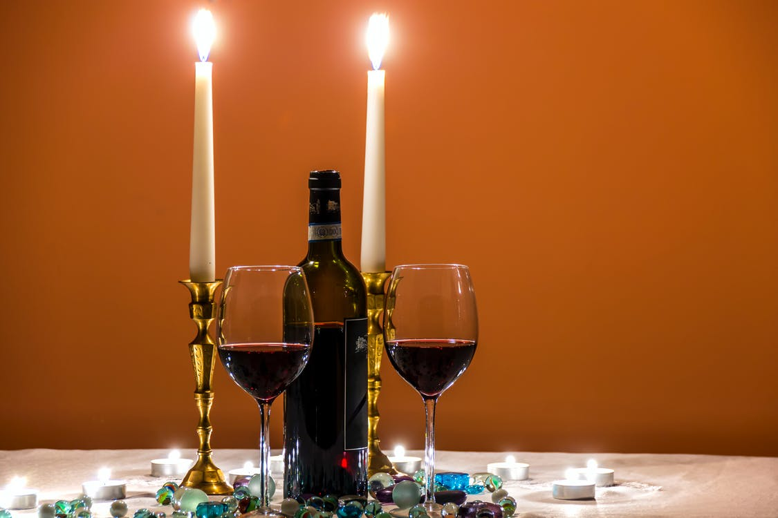 Two Almost Empty Long Stem Wine Glasses Beside Wine Bottle and Lighted Candles